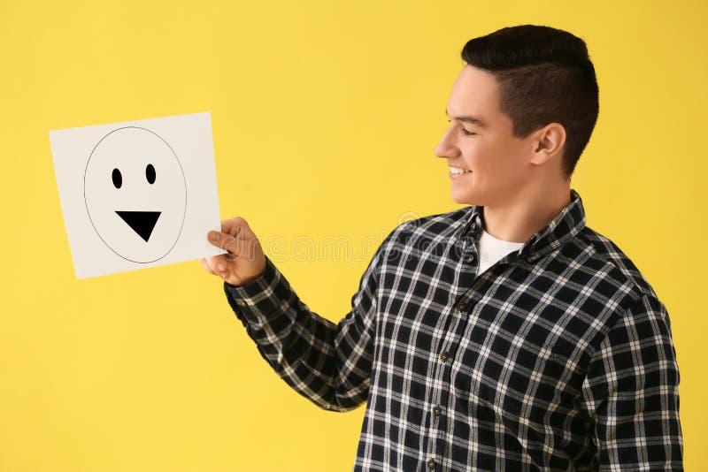 Holdingblatt papier des jungen Mannes mit gezogenem Emoticon auf Farbhintergrund lizenzfreie stockbilder
