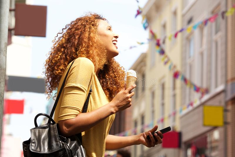 Holdingeistüte und -Handy der jungen Frau in der Stadt lizenzfreie stockbilder