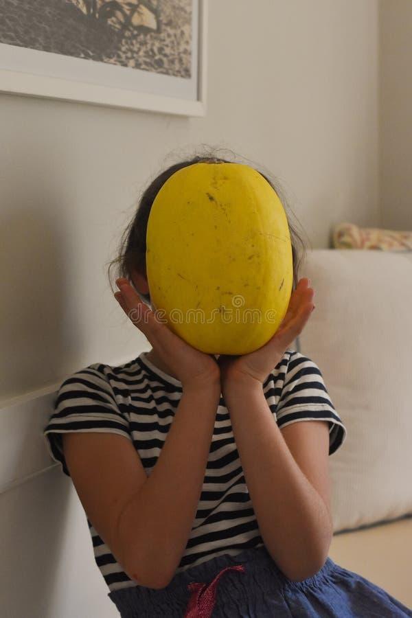 Holdinggemüse des jungen Mädchens vor Gesicht in einem weißen Wohnzimmer stockbild