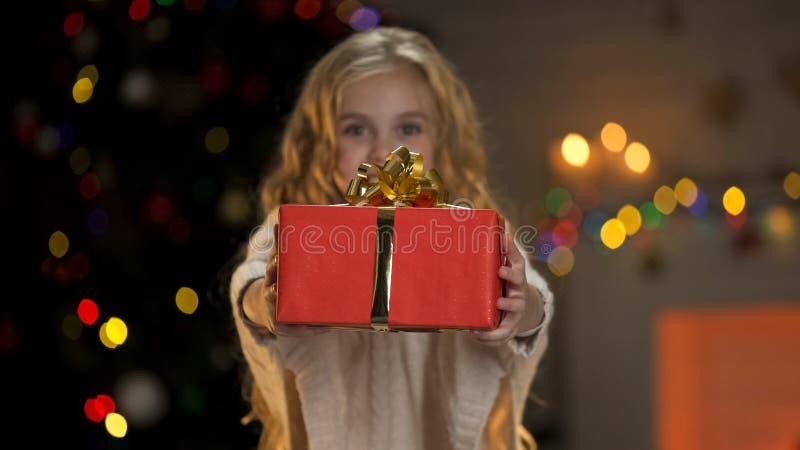 Holdinggeschenkbox des kleinen Mädchens, Geschenke mit verwaisten Kindern an Weihnachten teilend stockfoto