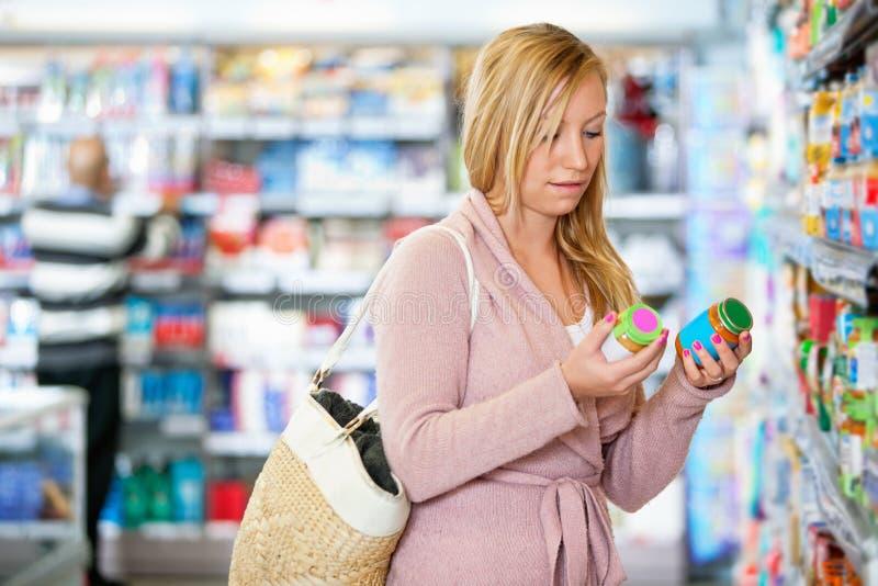 Holdingglas der jungen Frau im Supermarkt lizenzfreie stockbilder