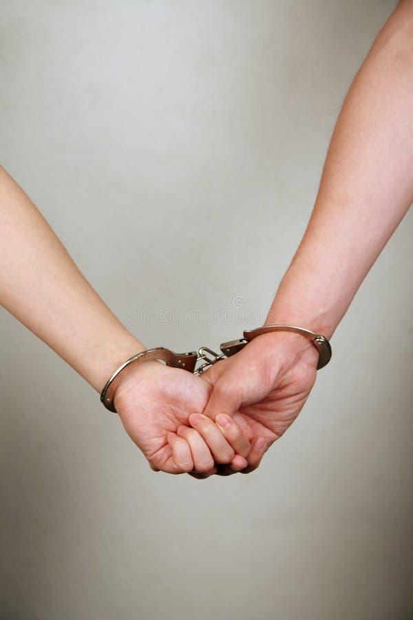 Holdinghände des männlichen und weiblichen Gefangenen stockbild