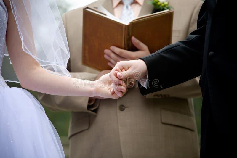 Holdinghände während einer Hochzeitszeremonie stockfotografie
