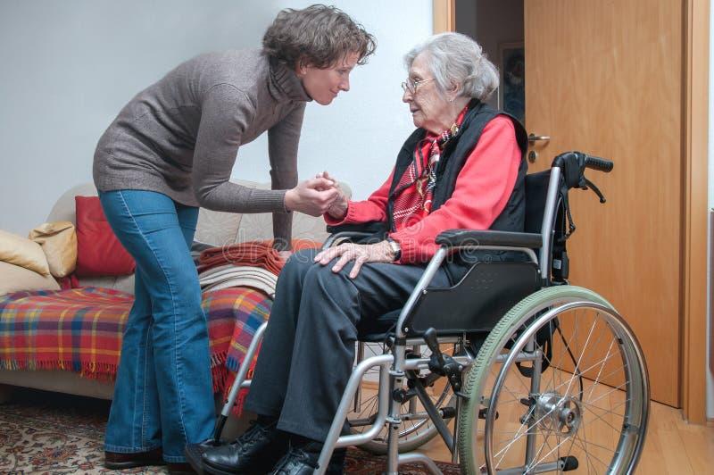 Holdinghand der jungen Frau der traurigen älteren Frau mit Rollstuhl stockbilder