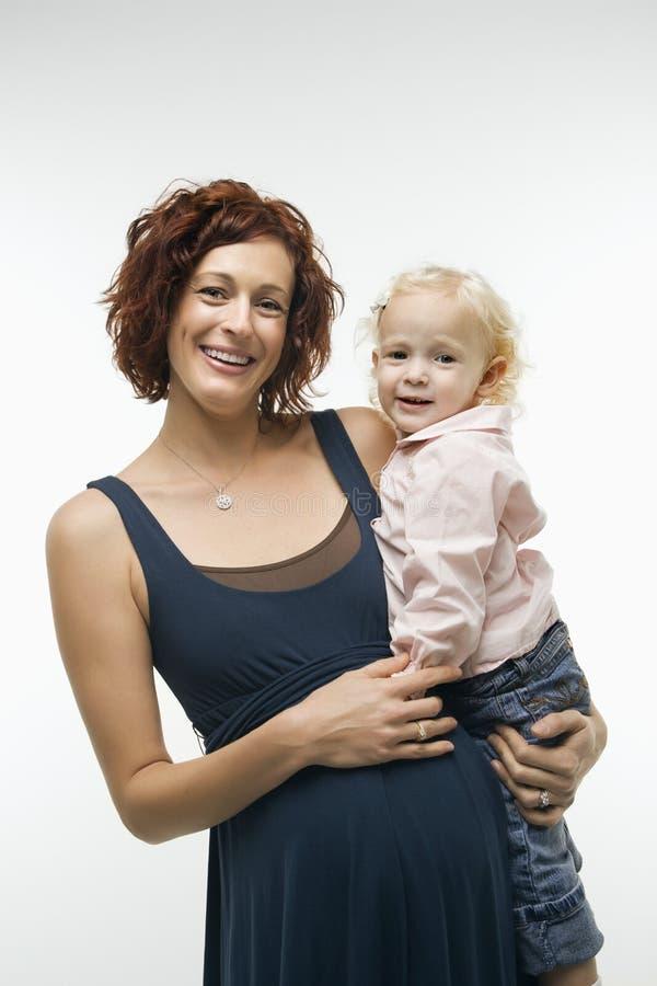 Holdingkind der schwangeren Frau. lizenzfreie stockbilder