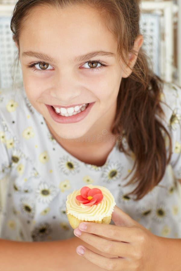 Holdingkleiner kuchen des jungen Mädchens lizenzfreies stockfoto