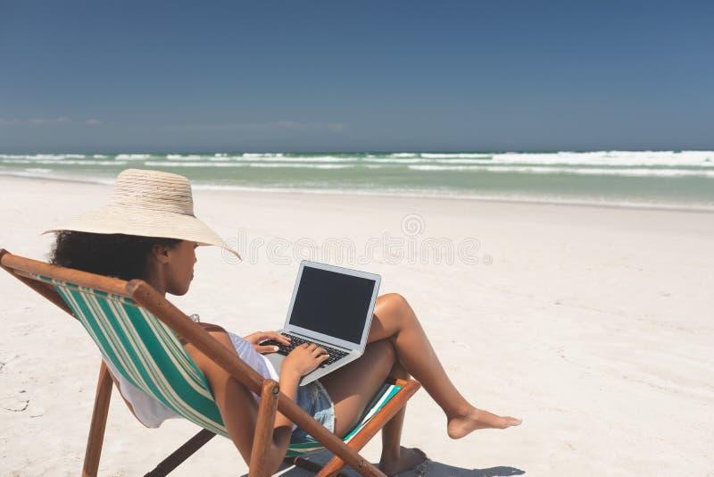 Holdinglaptop der jungen Frau beim Sitzen auf Sonnenruhesessel am Strand stockbild