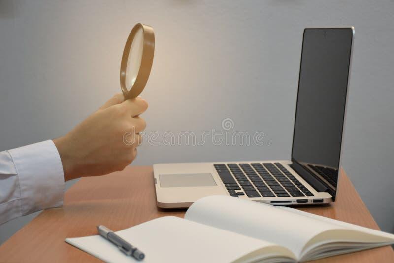 Holdinglupen-Suchnotizbuch des Geschäfts männliches Handund Laptop oder Computer für kreatives Konzept der Idee stockbild