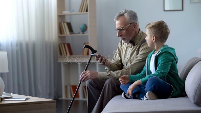 Holdingmobiltelefon des alten Mannes, Junge, der ihm zur Bekanntschaft mit neuen Technologien hilft stockbilder
