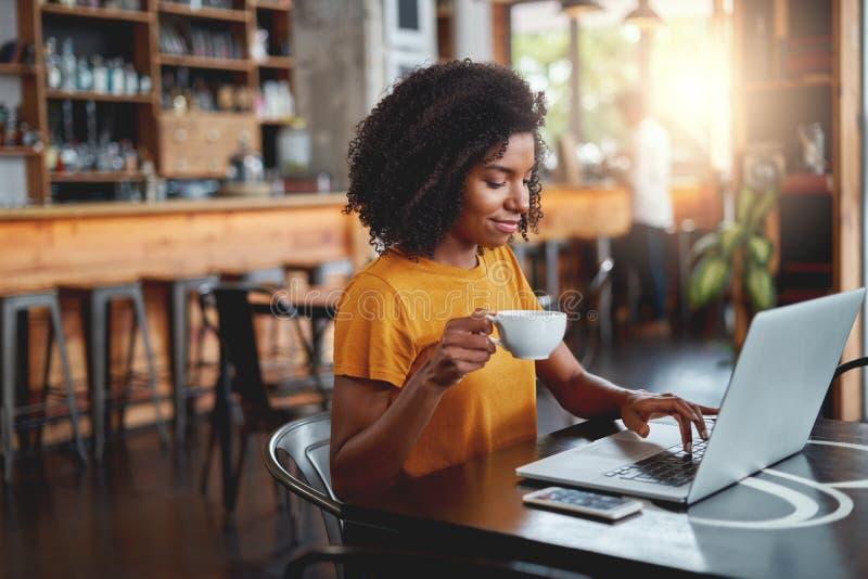 Holdingschale der jungen Frau in der Hand unter Verwendung des Laptops stockfotografie