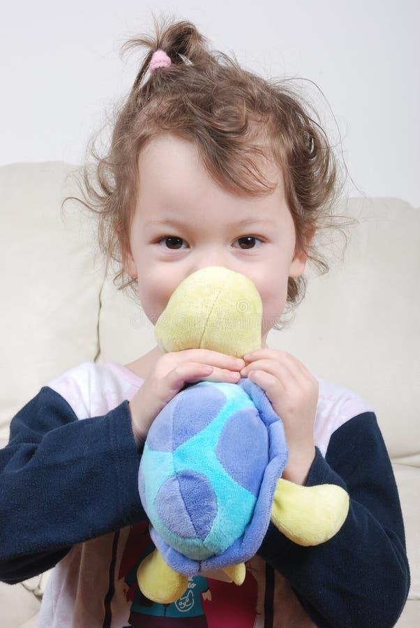Holdingschildkröteplüsch des kleinen Mädchens lizenzfreie stockbilder
