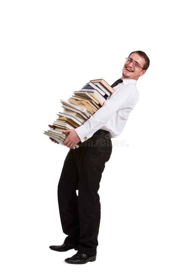 Holdingstapel des jungen Mannes Bücher stockbild