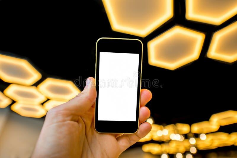 Holdingstelefoon op de moderne lichte achtergrond stock afbeelding