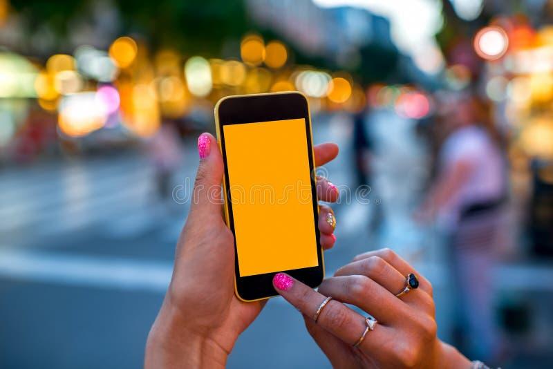 Holdingstelefoon op straatachtergrond stock afbeelding