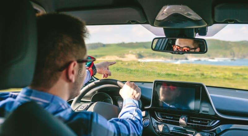 Holdingsteuerung des jungen Mannes und Zeigen des fahrens stockbild