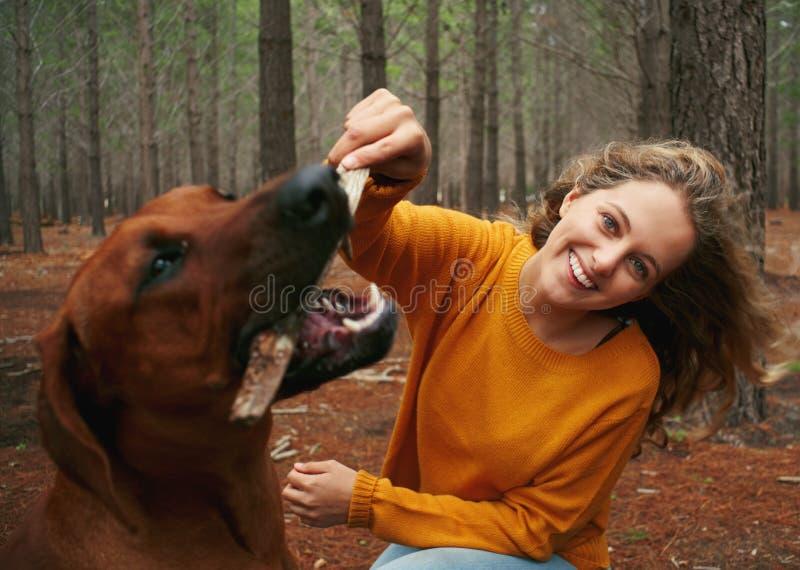 Holdingstock der jungen Frau in ihrem Hundemund stockbild