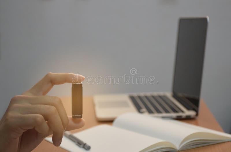 Holdingtrockenbatterie-Suchnotizbuch des Geschäfts männliches Handund Laptop oder Computer für kreatives Konzept der Energieidee stockbilder