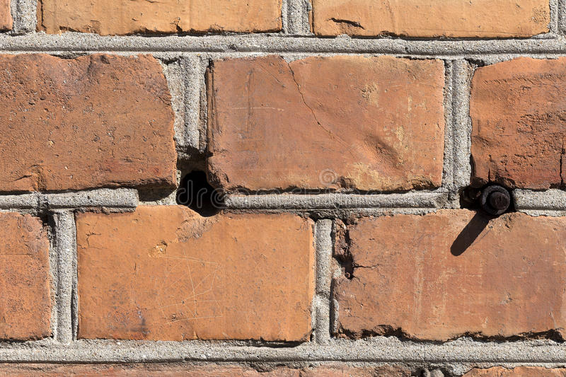 Hole and bolt. A detailed photo of a brick wall with all the damaged parts and the plaster. This one also have a hole and a bolt sticking out royalty free stock image