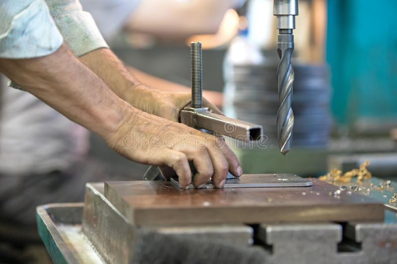 Hole boring on pillar drill machine with drill bit cutting tool royalty free stock photography