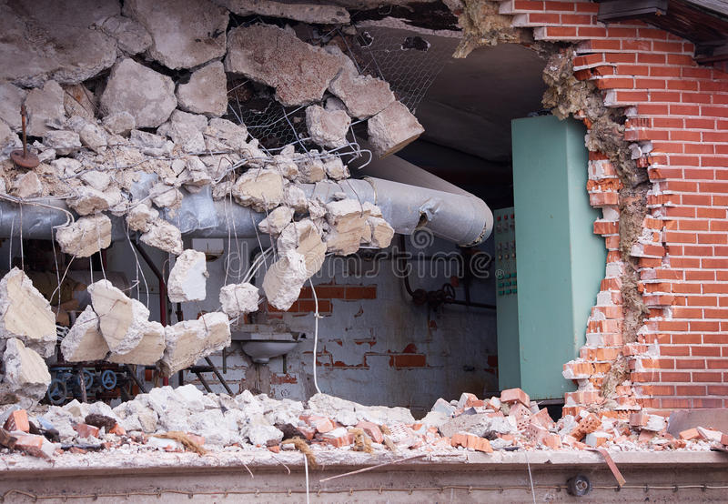Hole in the brick wall of wrecked building at demolition site stock image