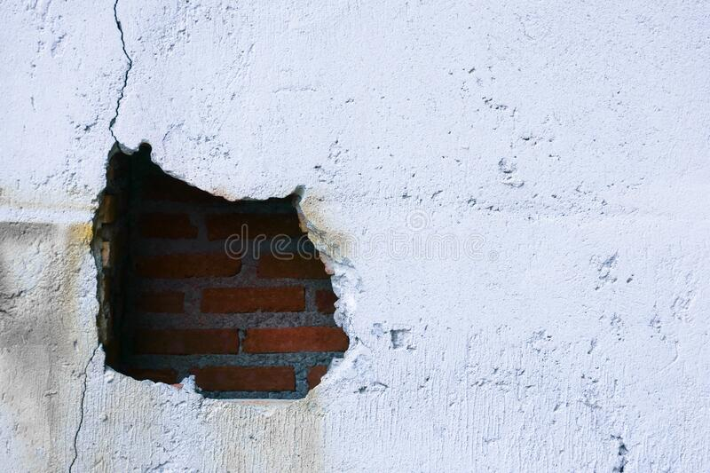 Hole in broken wall and old bricks on a white background. Large crack on the wall of an old brick house, crumbling plaster and royalty free stock photography