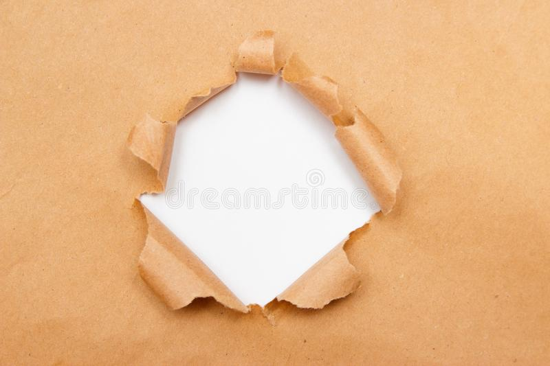 Hole into brown craft paper sheet with torn edges. White center isolated, clipping path included. Top view royalty free stock images