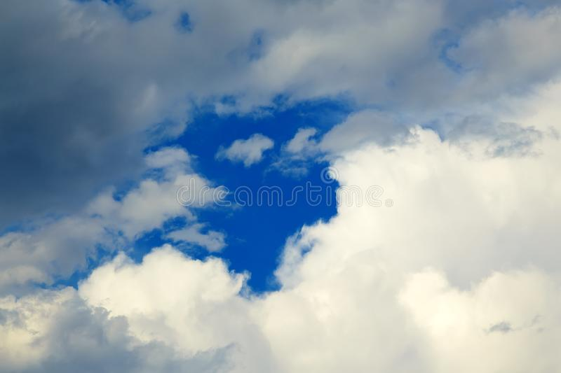 Hole in the clouds. Beautiful white clouds on blue sky with holes in center. stock photos