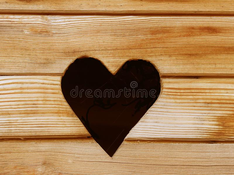 A hole in the form of a heart cut out in a plane consisting of dry boards. A symbol of love and relationship. Romantic mood. Handm. Ade. Express your feelings stock image