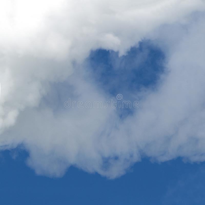 A hole in the form of a heart in a white cloud against a blue sky. A square picture. Background for design. Copy space. stock images