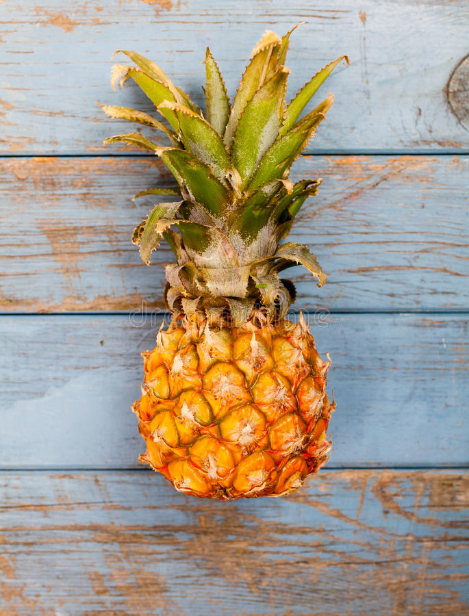 Hole fresh pineapple on blue wooden background. From above stock photography