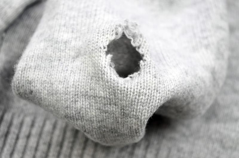 Tear in knit fabric, close up. Hole on the grey sweater. Texture of woolen fabric of an old sweater stock image