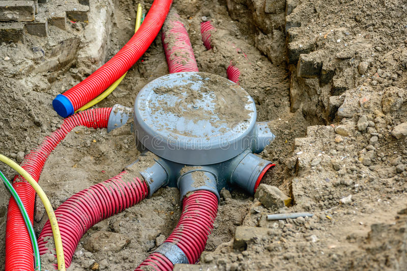 Hole in the ground with a node of flexible plastic conduits stock images