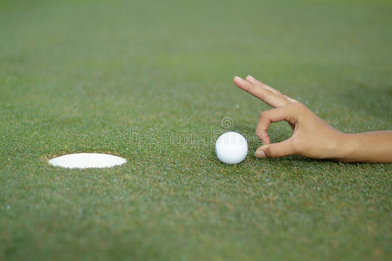 Hole-in-one 2. Hand pushing a golfball into the hole royalty free stock photos