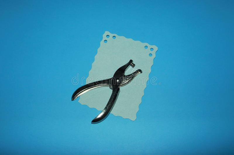 Hole punch and a blue sheet of paper with holes royalty free stock photography