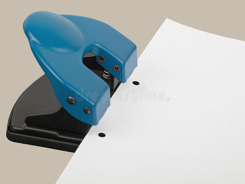Hole punch. Drilling hole punch with paper, studio shot stock photo
