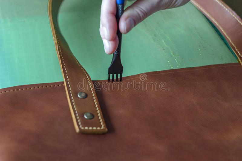 Hole punch tool in a female hand while working with a leather bag. A hole punch tool in a female hand while working with a leather bag stock photos
