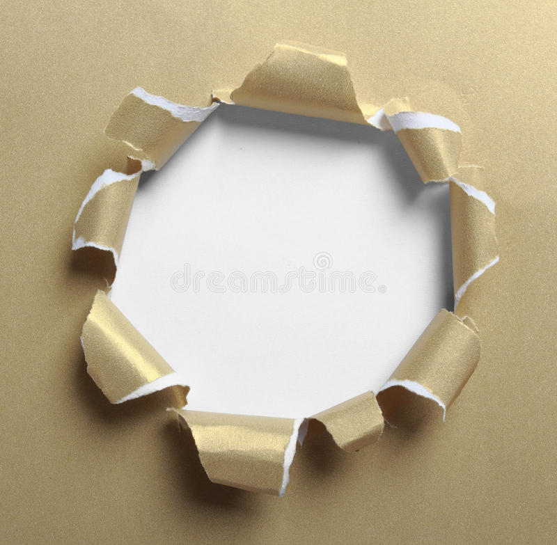 Hole ripped in gold paper. On white background stock photography