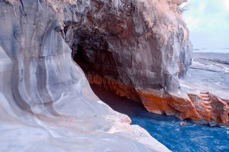 A hole in the rock in a cliff near a beach stock photo