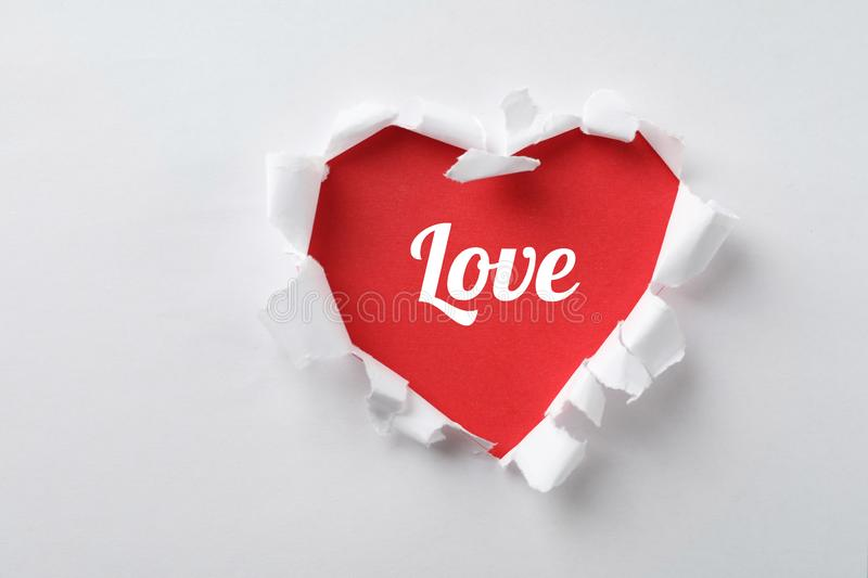 Hole in shape of heart with word LOVE on white paper. Valentines Day celebration royalty free stock photos