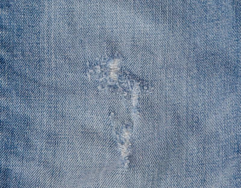 Hole and Threads on Denim Jeans. Ripped Destroyed Torn Blue jeans background. Close up blue jean texture stock images