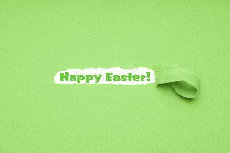Happy Easter. Hole torn in green paper background to reveal Happy Easter greeting royalty free stock images