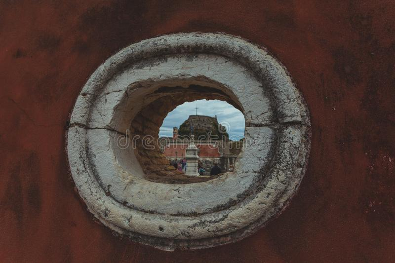 Hole in a wall with the entrance to the old Venetian fortress of Corfu in the background royalty free stock photo