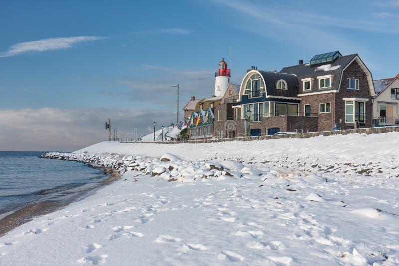 Holender plaża zakrywająca z śniegiem i widokiem przy latarnią morską Urk fotografia stock