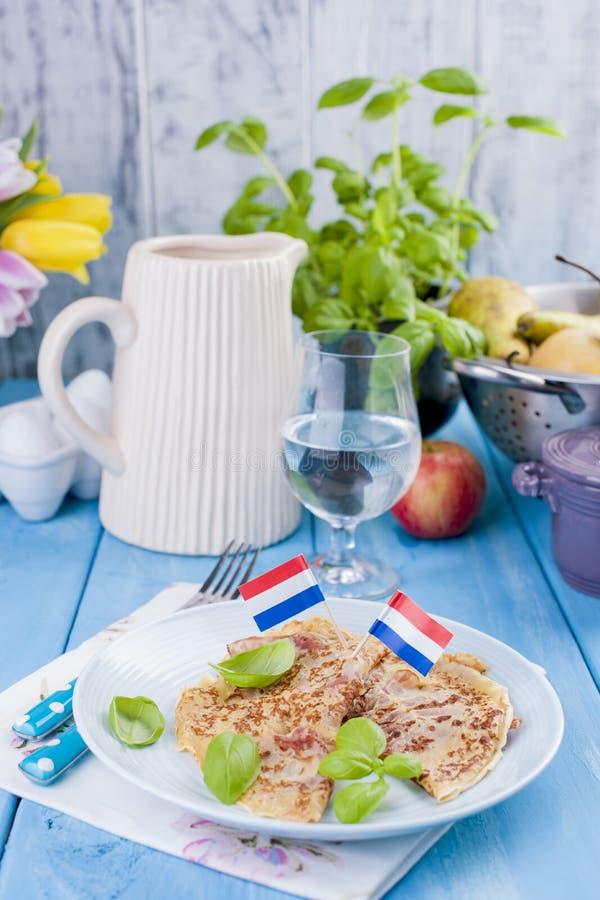 Holenderscy bliny z baleronem dla śniadaniowych Jaskrawych kolorów, błękitny tło Smakowity i caloric E fotografia stock