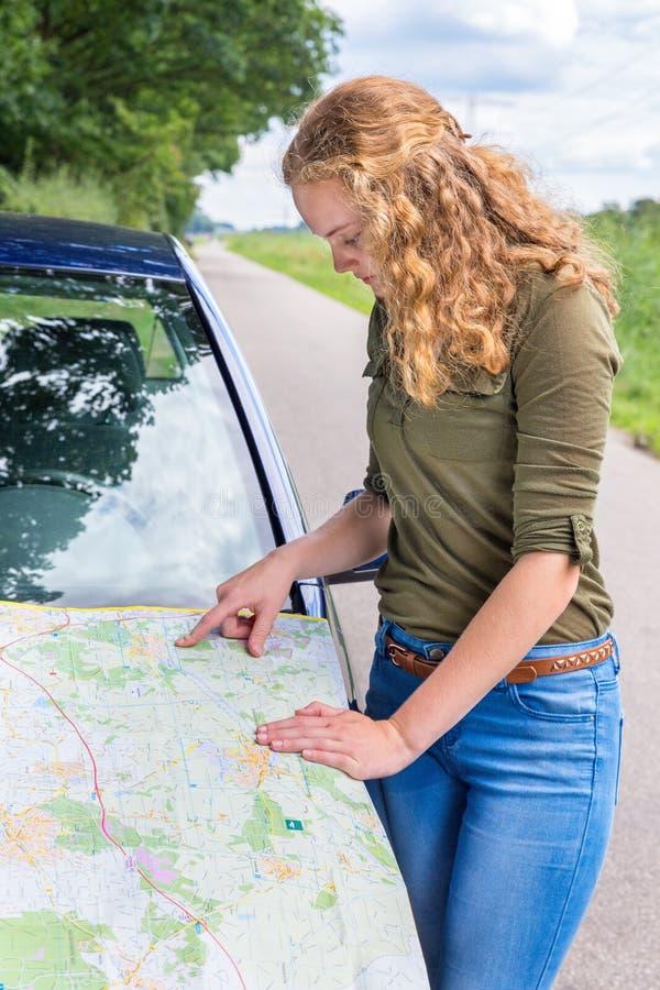 Holenderska kobieta czyta drogową mapę na samochodowym kapiszonie obrazy stock