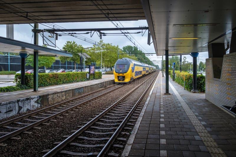 Holenderski intercity pociąg przyjeżdża przy stacją kolejową obrazy royalty free