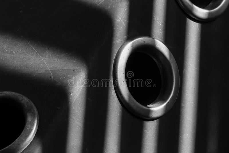 Holes on the metal panel. Wood stove for heating the house. Household Geometry. Black and white, holes and lines, backgrounds and textures, metal surface royalty free stock images