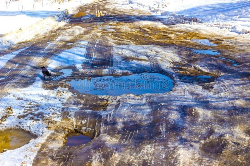 Holes and pothole on a rural road with snow royalty free stock photo