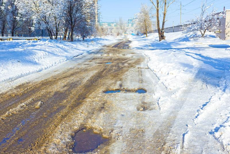 Holes and pothole on a rural road with snow royalty free stock images