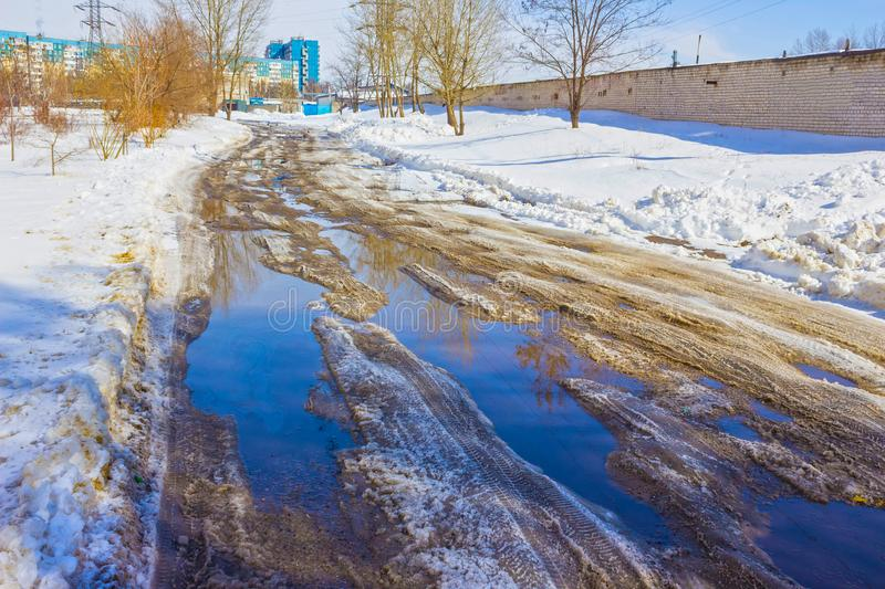 Holes and pothole on a rural road with snow royalty free stock image